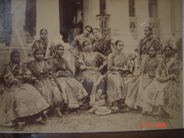 A postcard photograph of 11 dancing girls sitting together