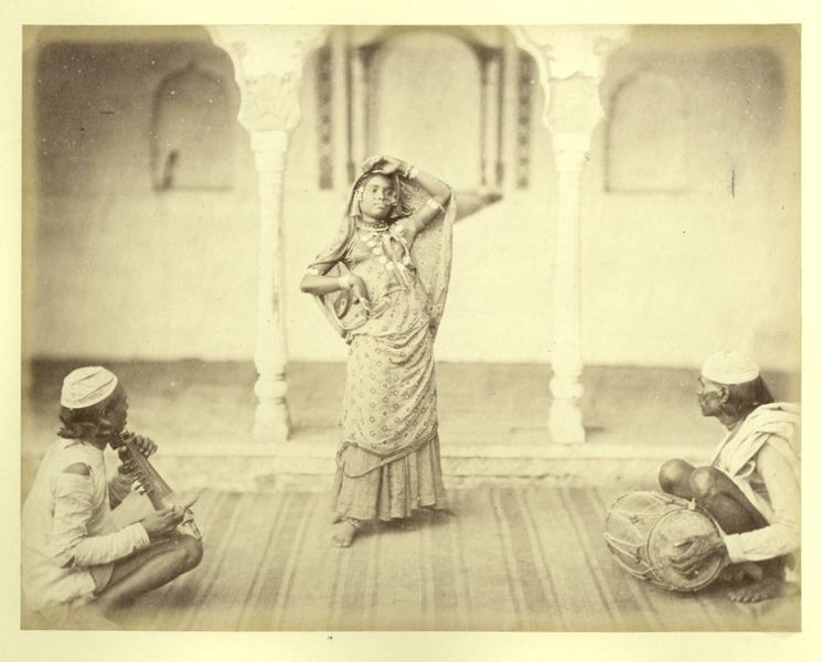 A photograph of a dancing girl and two musicians performing together