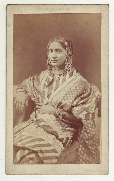 A studio photograph of a seated dancing girl