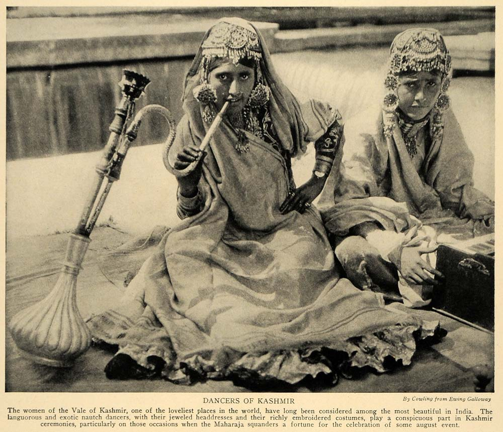 "A photograph of two young dancing girls. The image caption reads: ""The women of the Vale of Kashmir, one of the loveliest places in the world, have long been considered among the most beautiful in India. The languorous and exotic nautch dancers, with their jeweled headdresses and their richly embroidered costumes, play a conspicuous part in Kashmir ceremonies, particularly on those occasions when the Maharaja squanders a fortune for the celebration of some august event."""