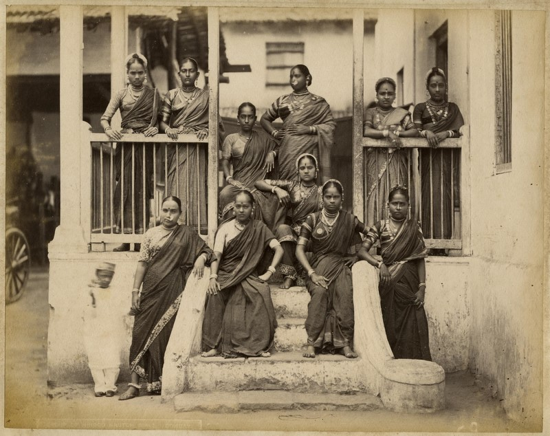 A photograph of nautch girls standing around a porch in Bombay