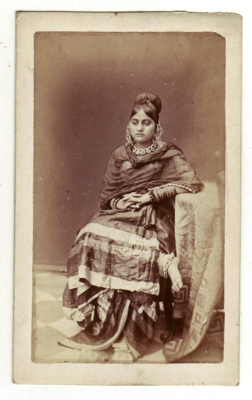 A posed photograph of a seated dancing girl in Lucknow