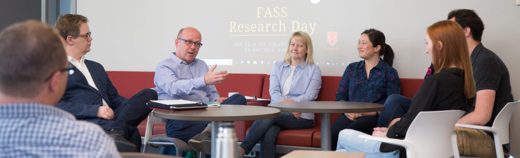 Huron faculty members sit around a table in the library, discussing research during FASS Day 2018.
