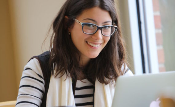 A smiling student with dark hair works at her laptop in the Huron library. She is wearing glasses, a long-sleeved shirt, and a scarf.