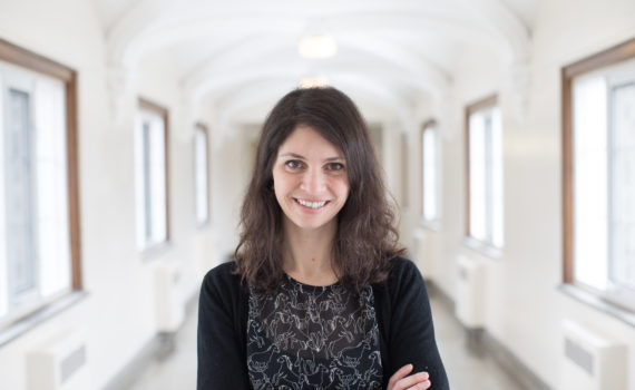 A bright, smiling headshot of Dr. Kate Lawless, CGS professor. She has brown, wavy hair and is wearing a dark dress. She is standing in a hallway at Huron University College.