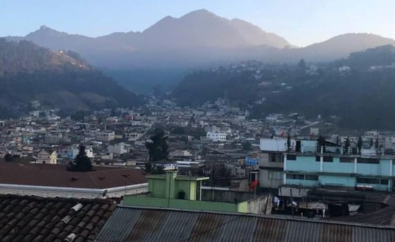 A landscape photo of the tops of houses in Guatemala. Foggy mountains are in the background.
