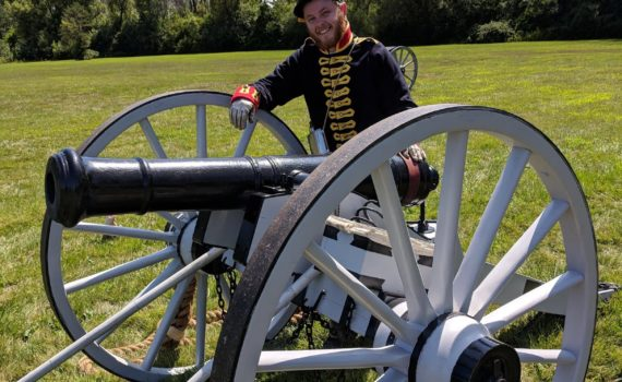 CURL Fellow Patrick Kinghan stands behind a cannon, wearing civil war re-enactment attire.