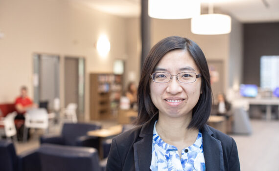 A smiling photo of Dr. Yan Lu. She has shoulder-length dark hair and a blue blazer on, and she's standing in the Huron Library Commons.