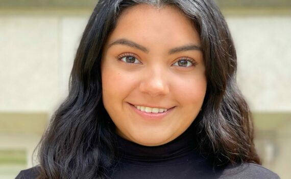 A smiling photo of Ivania Salmeron. She is a Huron student with long, dark hair. She is wearing a black turtleneck.