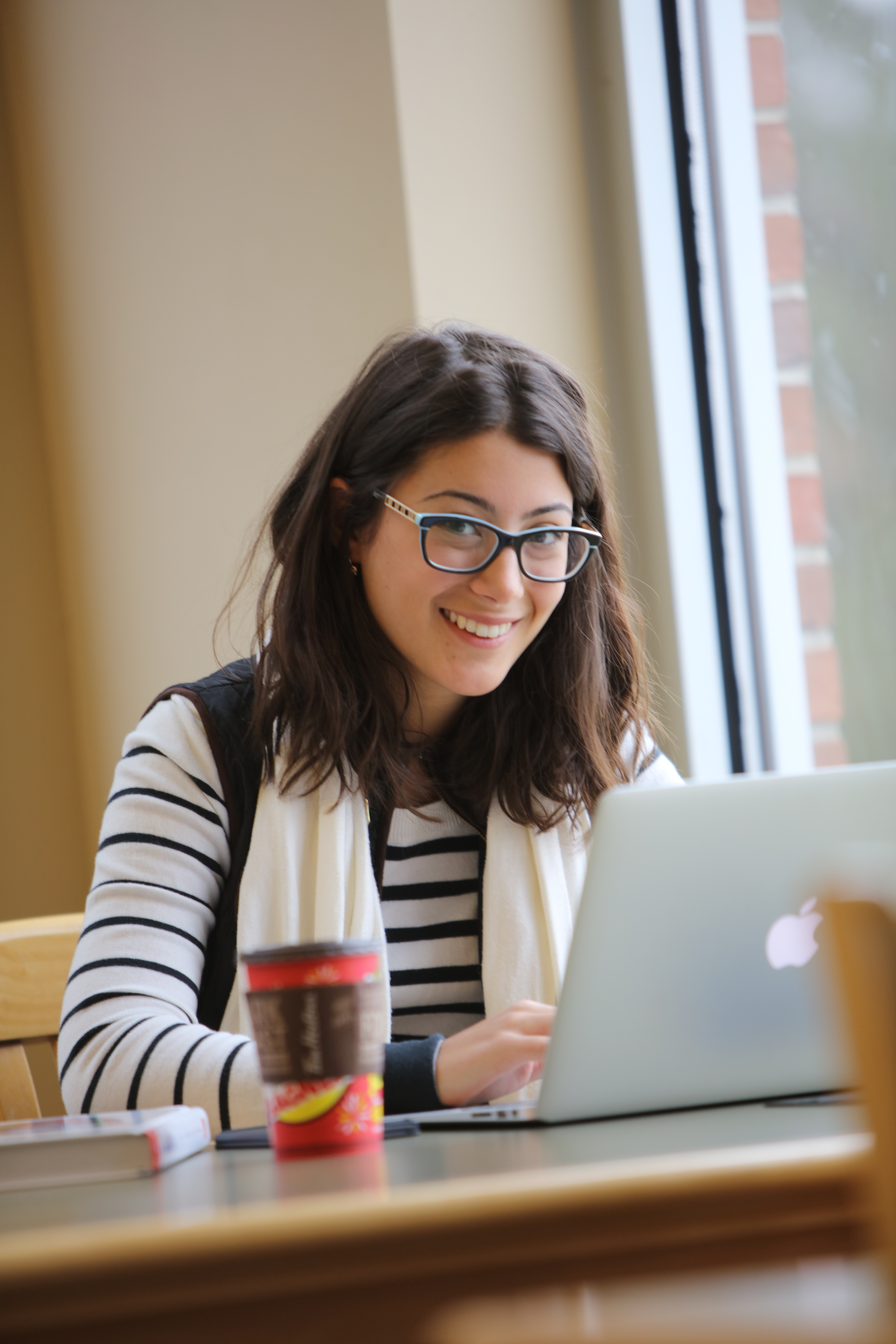 A smiling student sits at her laptop, working in the Huron library.